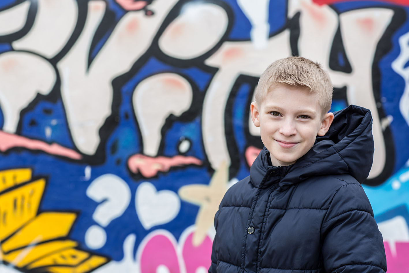 A child in front of a graffiti wall