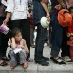 Eradicate Poverty, child waits in a queue for food